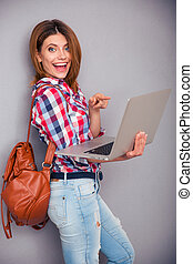 Young woman pointing finger on laptop screen - Cheerful...