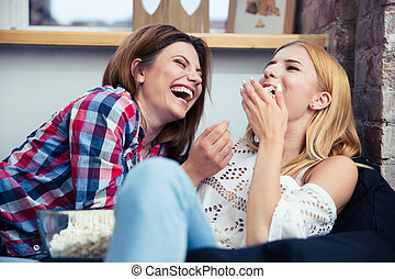 Girls lying on the sofa and eating popcorn - Two cheerful...