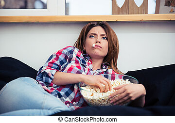 Young woman eating popcorn - Young woman lying on the sofa...
