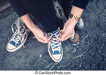 Hipster wearing sneakers, teenager tieing laces at sport shoes. Urban lifestyle with footwear and modern clothing.