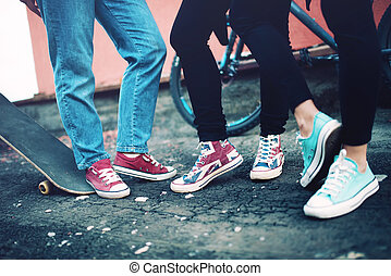 Close up of modern sneakers worn by friends, urban lifestyle of modern clothing and footwear