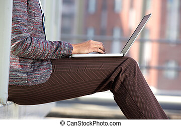 Business woman typing on laptop outside - Side portrait of a...