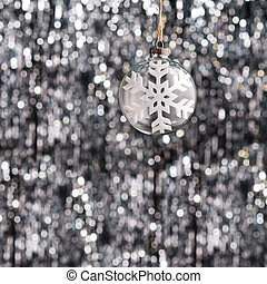 Snow flake Christmas bauble over silver glitter background
