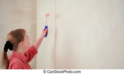 A Pretty Blonde Paints The Wall Pink.