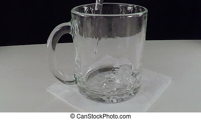 Mineral Water in a Glass Cup. Slow Motion. Bubbles of Carbon...