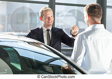 Salesman giving car key - Smiling salesman giving car key to...