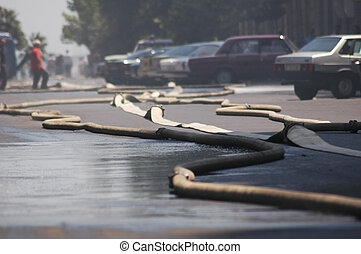 Fire hoses stretching across the street during fire in the...