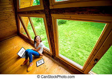 Woman sitting on the floor in wooden house - Woman in jeans...