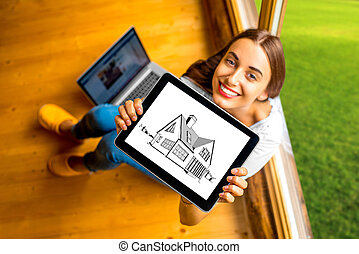 Woman showing digital tablet in the wooden house - Young and...