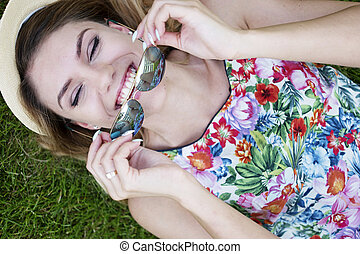 Happy Woman Holding Shades While Lying on Grasses - Close up...