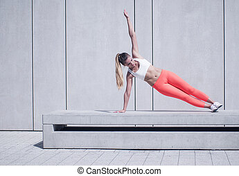 Sporty Woman Doing Side Plank Exercise on Platform