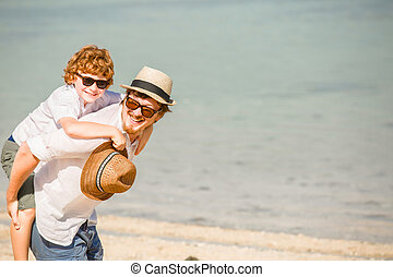 Hipster father with beard and red haired son playing on the beach at a sunny day. Concept of friendly family