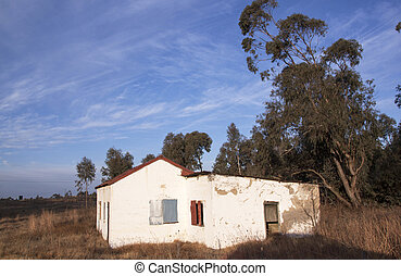 Dilapidated White Rural Building With Boarded Windows