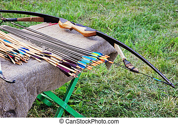 Bow and arrows on small table. - Bow and arrows on small...