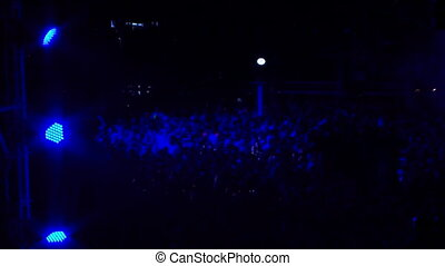 Huge Crowd Of People Dancing Illuminated With Blue Lights At...