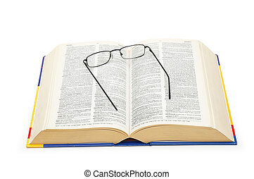 Spectacles over the open dictionary isolated on white