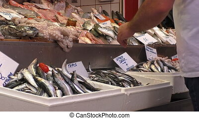 Greek fish market - Fishmonger or fish seller is looking...