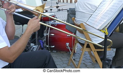 Man Playing Trombone - Man is playing on trombone along with...