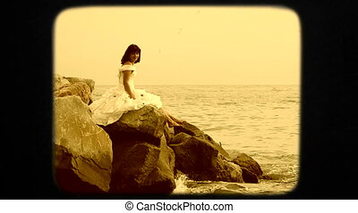 Young Woman In White Dress Sitting On Rock By Sea