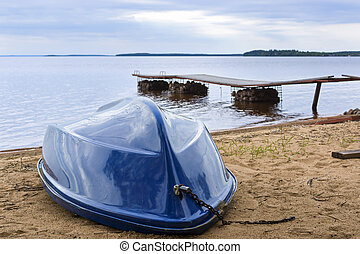 Boat on wild lake beach in summer