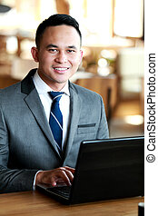 businessman smiling while doing his job on laptop