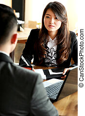 businesswoman writing information from her client on...