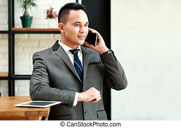 businessman talking on the phone - young businessman talking...
