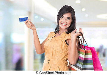 happy Asian woman holding shopping bags and credit card