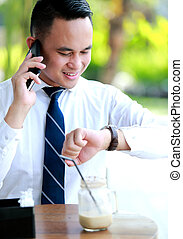 businessman talking on the phone while looking at his...