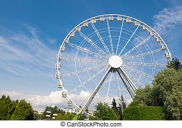 modern white ferris wheel against blue sky background