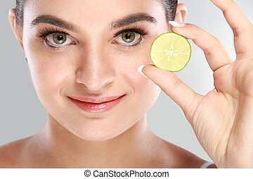 beautiful face of woman holding a slice of lime