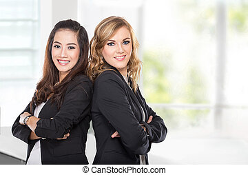 Two young businesswoman smiling while leaning againts each...
