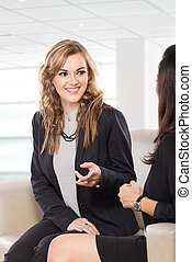 Two friendly businesswomen sitting and discussing new ideas,...