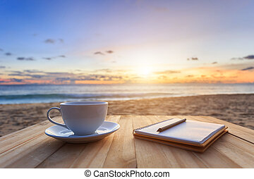 Coffee cup on wood table at sunset or sunrise beach - Close...