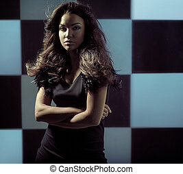 Alluring woman standing over the chessboard background -...