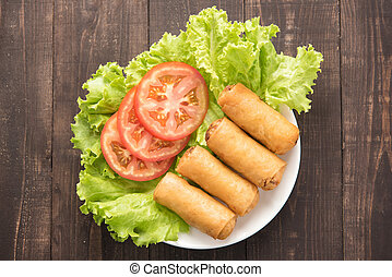 Fried Chinese traditional spring rolls on wooden background....