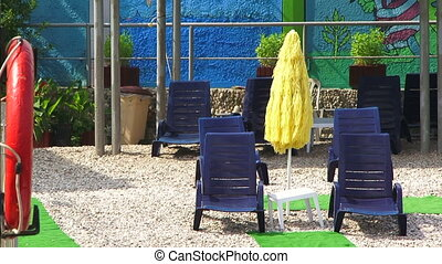 Rows Of Blue Chaise Longues Standing On The Pebble Beach -...