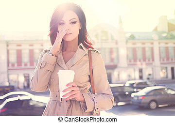 Early coffee. - Beautiful young woman in a modern trench...