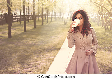 Take-out coffee. - Beautiful young woman in a modern trench...
