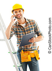 Cheerful repairman. Smiling young manual worker talking on...