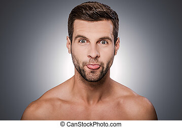 Funny grimace Portrait of handsome young shirtless man...
