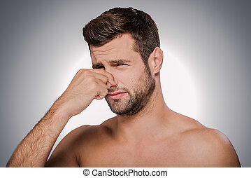 This awful smell! Portrait of frustrated young shirtless man...