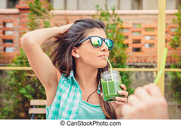 Woman with sunglasses drinking green vegetable smoothie...