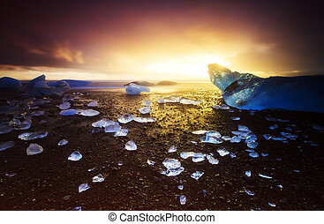 Black ice sunset beach - Beautiful beached chunks of ice at...