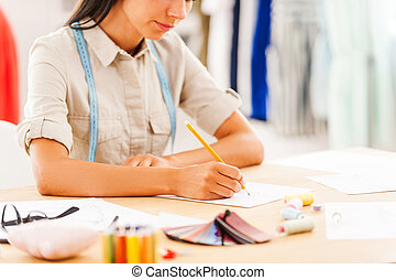 Creating masterpiece. Close-up of young woman drawing while sitting at her working place