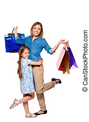 Happy a mother and daughter with shopping bags standing at...
