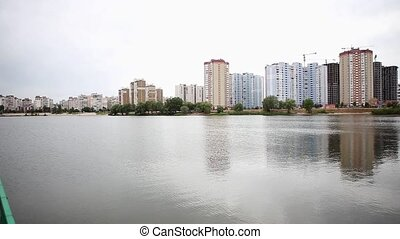 apartment buildings reflected in lake