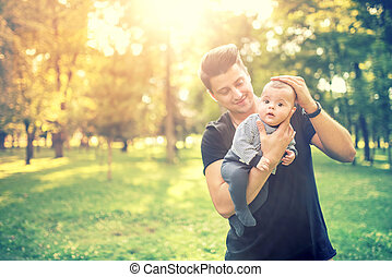 happy young male, father holding 3 months old infant and...