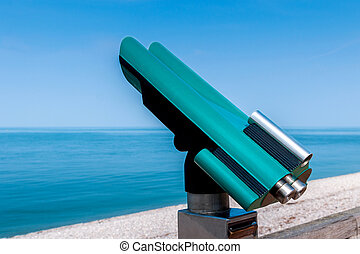 Public telescope at seaside in turquoise colors and with...