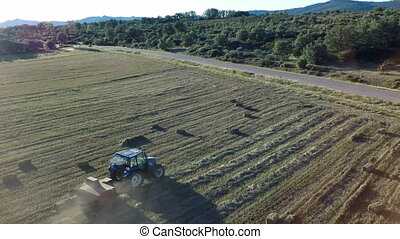 Aerial view of tractor preparing square bales - Tractor...